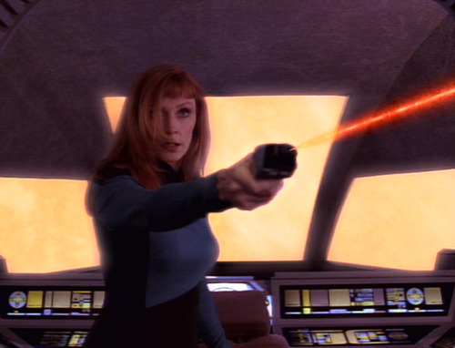 Crusher fires a phaser at Jo'Bril in the shuttle