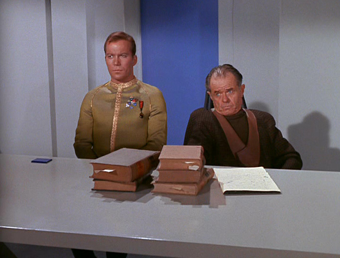 Kirk sits next to Cogley and his stack of books