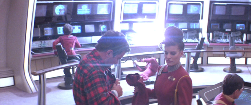 crewmember hands Kirk a uniform shirt as a console explodes in the background