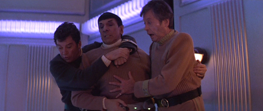 Kirk and McCoy hang on to Spock and look down