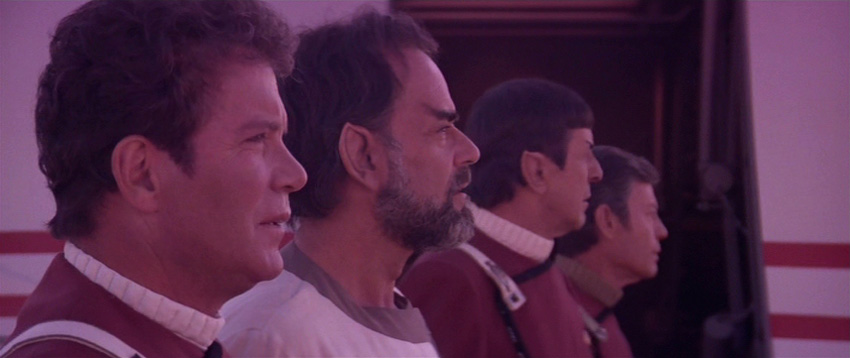 Kirk, Sybok, Spock and McCoy bathed in purple light