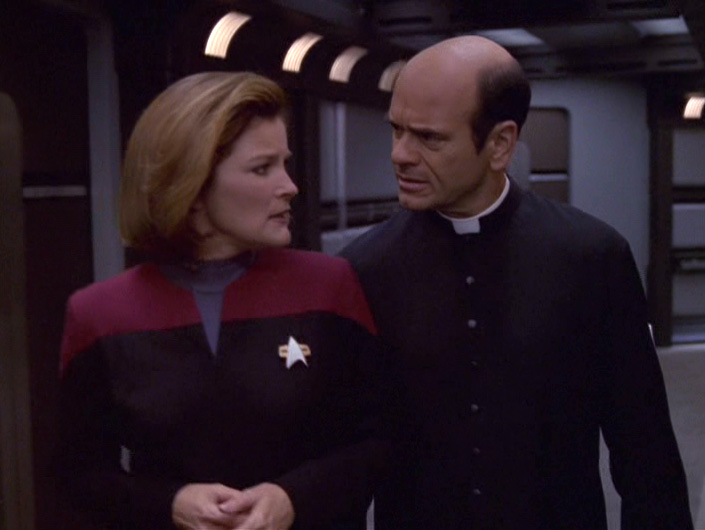 The Doctor dressed as his Priest character walks and talks with Janeway in the corridor