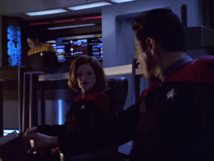Janeway and Chakotay sit on the dim bridge