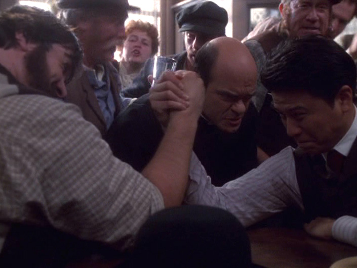 The Doctor oversees two men arm-wrestling