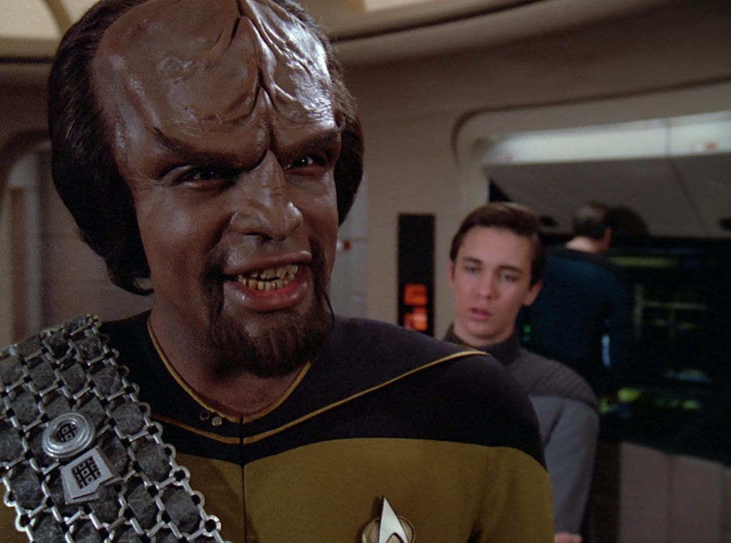 Worf talks about romancing, Klingon-style, while Wesley rolls his eyes