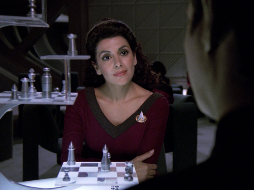 Troi stares at Data across the 3D chess board