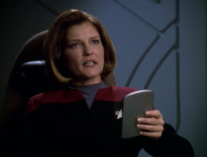 Janeway holds a padd and looks dismayed