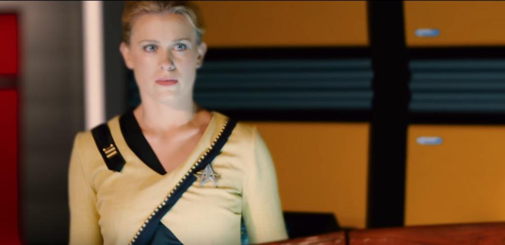 Woman in her Starfleet uniform - which has black edging that crosses over her torso