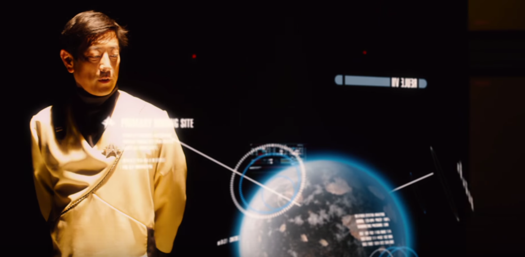 Grant Imihara as a Starfleet officer looking at a holographic projection of the planet