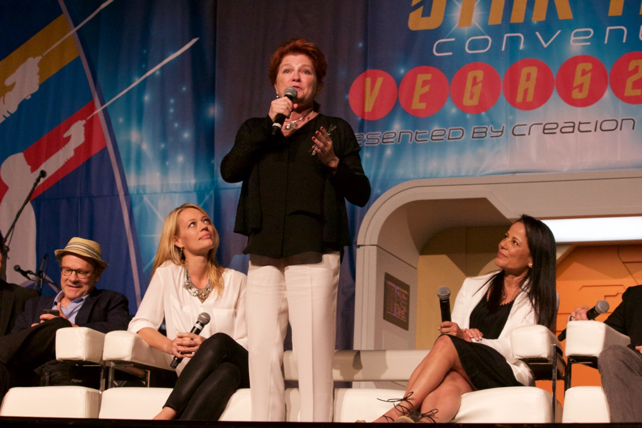 Kate Mulgrew standing up and speaking into her mic while Jeri and Roxann look up at her