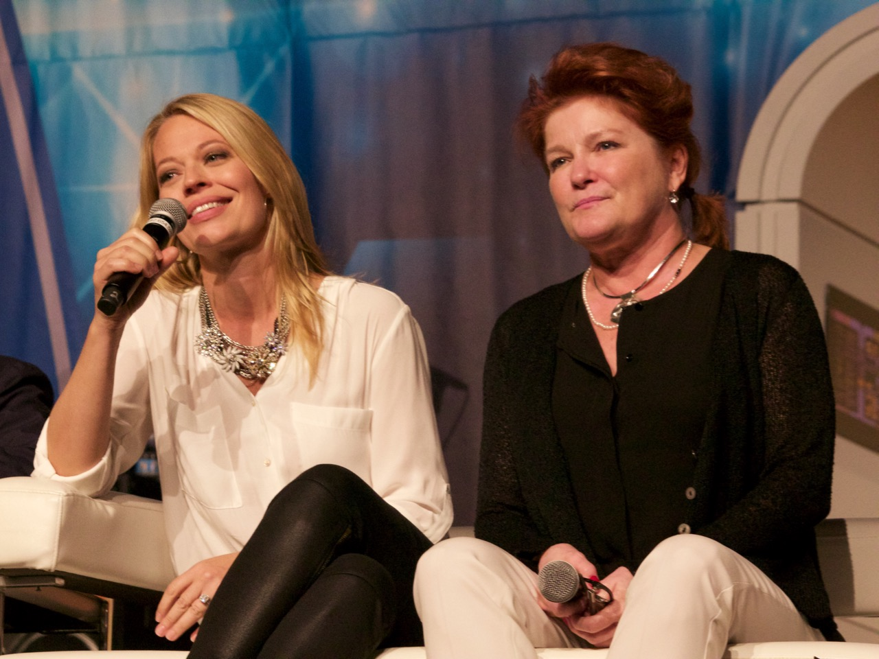 Jeri speaks into a microphone while Kate smiles