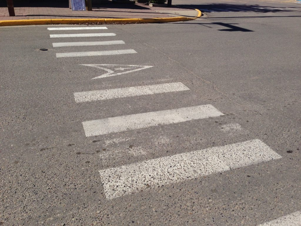 Crosswalk with Delta Shield painted in the middle