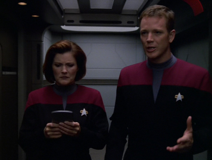Janeway looks concerned at the PADD Paris has handed her