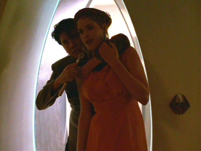 Harry holds what looks like a sonic screwdriver to a woman's neck