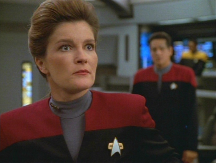 Janeway looks at Harry with shock and anger