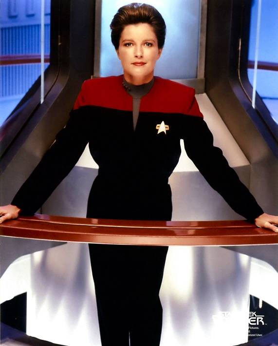 Janeway standing  in front of the warp core and leaning on the railing