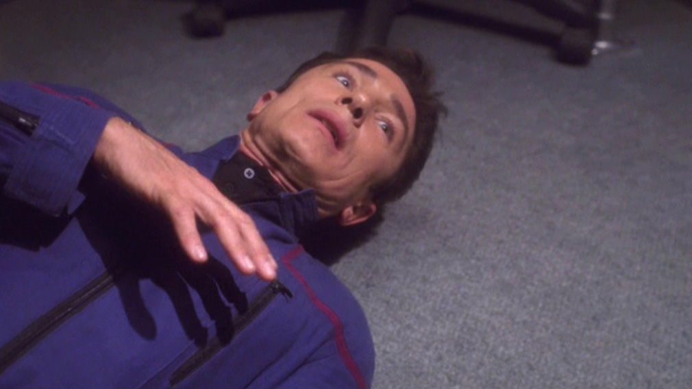Reed clutching his chest, lying on the floor