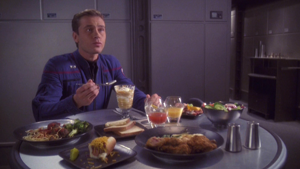 Trip sitting at a table full of food in the mess hall