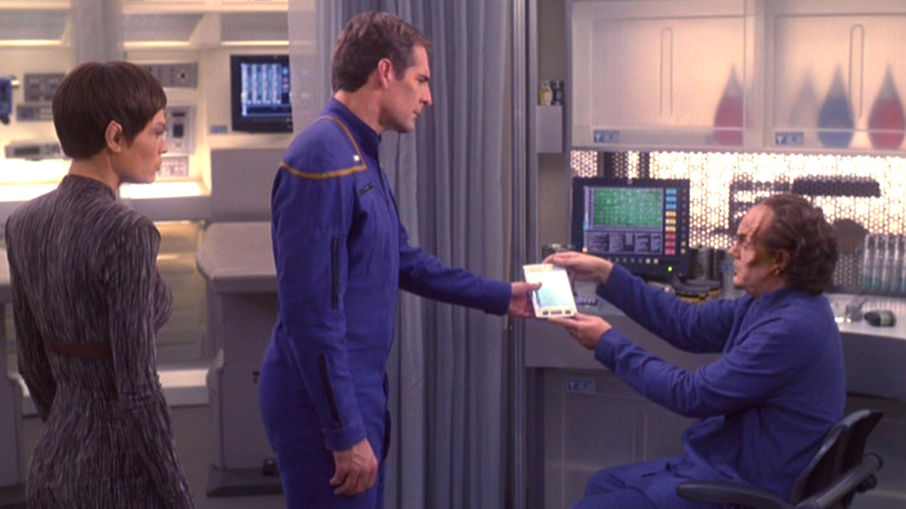 Phlox hands a padd to Archer while T'Pol looks on