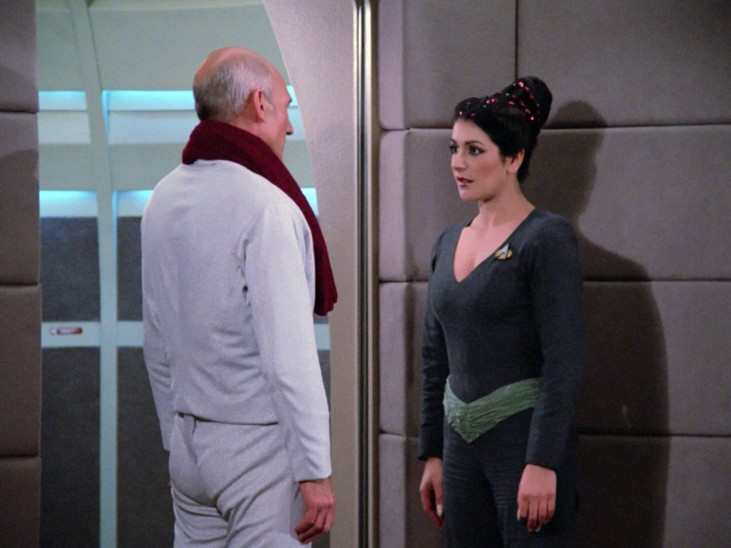 Troi speaks to Picard by the turbolift door after his fencing practice