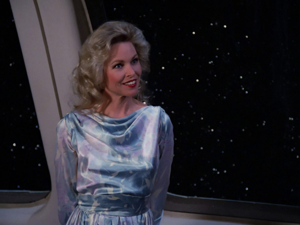 Jenice stands at the window of the Enterprise