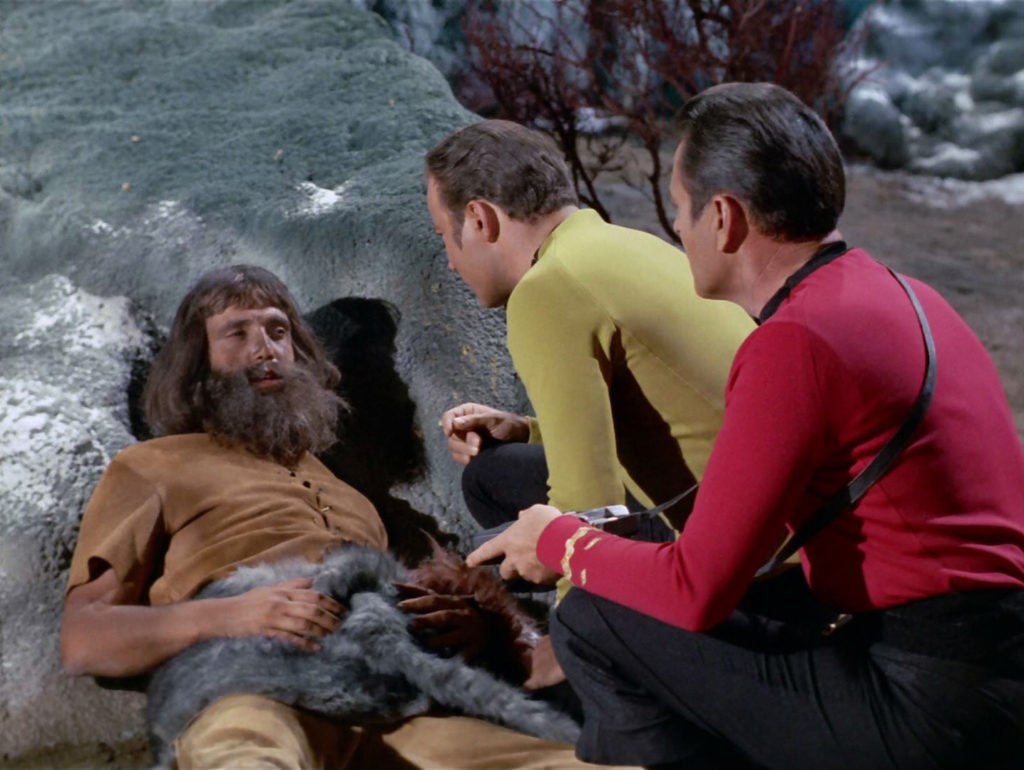 Kirk speaks to an injured Morg on the planet's surface. The Morg has long hair, a shaggy beard and is dressed in skins and furs.