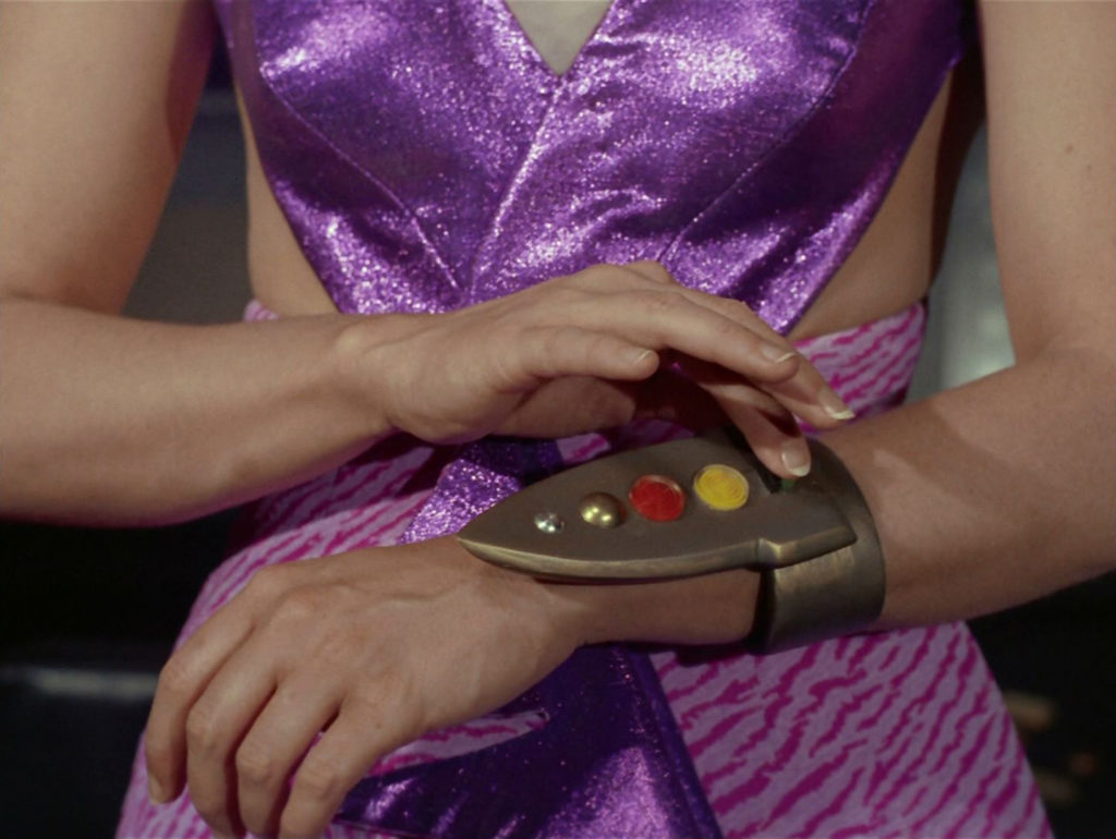 Kara presses a button on a wrist remote that she wears to control the pain belts