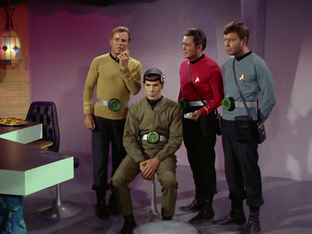 Kirk, Scotty and McCoy stand behind Spock in his brainless state