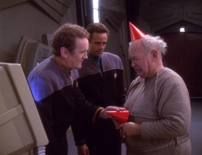 Patrick, an older man in a red paper birthday hat, tries to give a hat to Miles