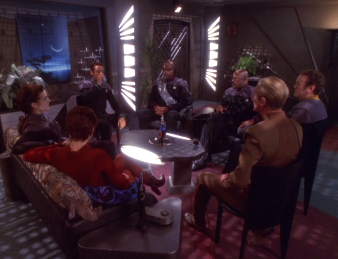 Bashir talks to the senior staff in Sisko's living room