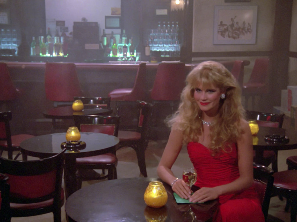 A blonde woman in a red dress sits in the holodeck jazz club