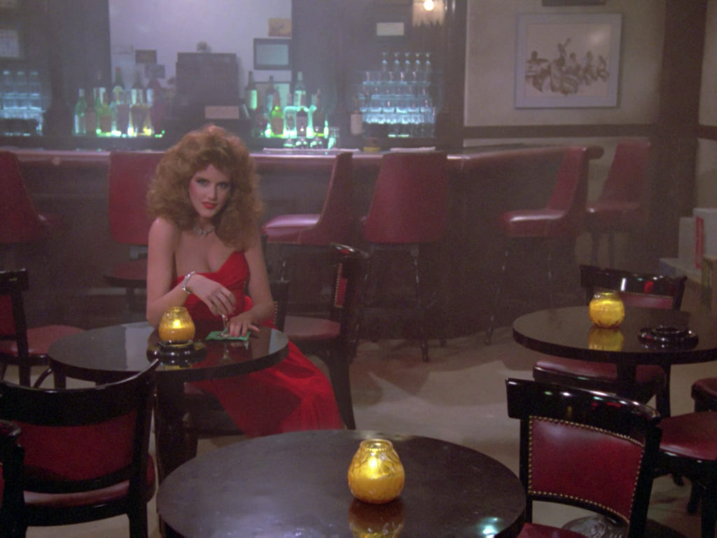 Woman with strawberry blonde perm in the same red dress in the holodeck bar