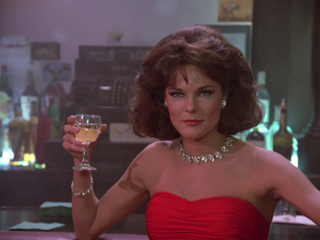 Minuet (Carolyn McCormack) at the bar with a cocktail
