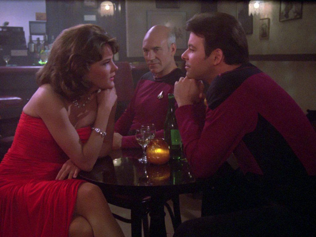 Minuet and Riker gaze at each other across a table while Picard watches