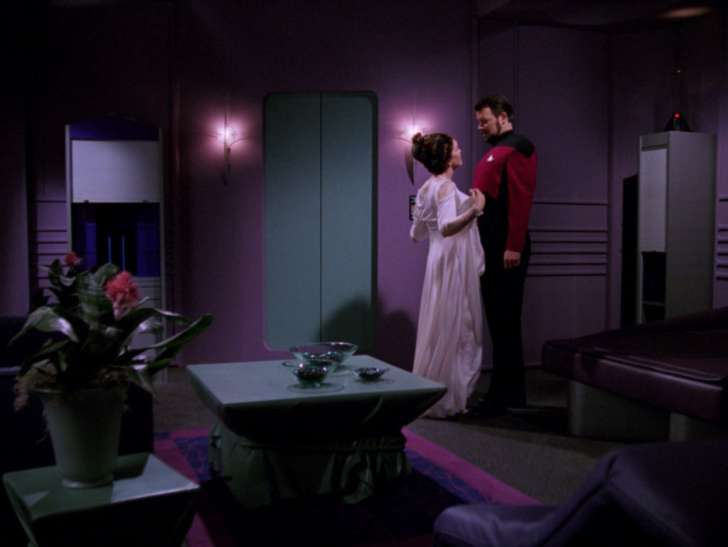 Manua stands close to Riker and starts to remove her robe