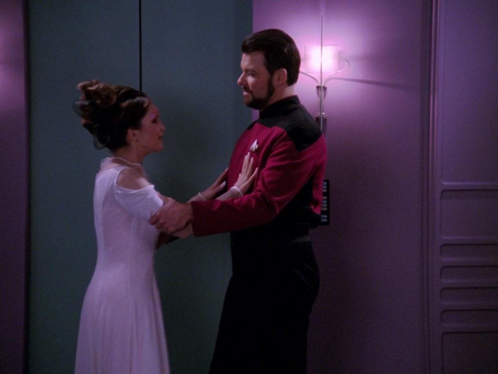 Manua tries to push Riker away as he grabs her arms