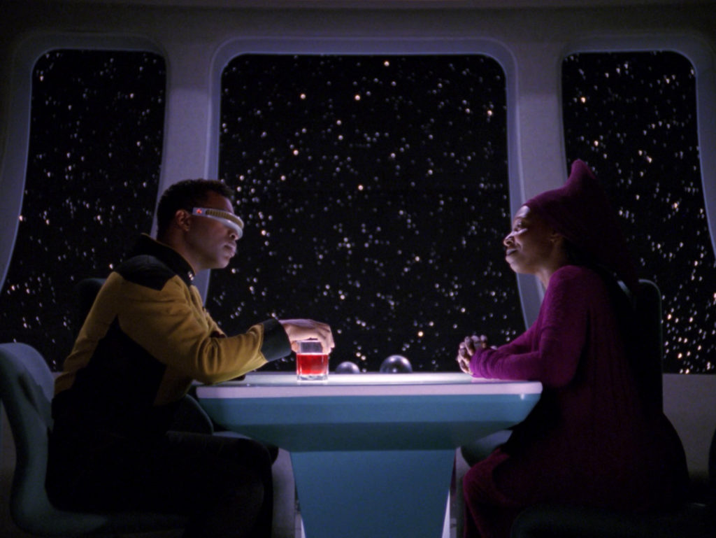 Geordi and Guinan sit across a table in 10 forward