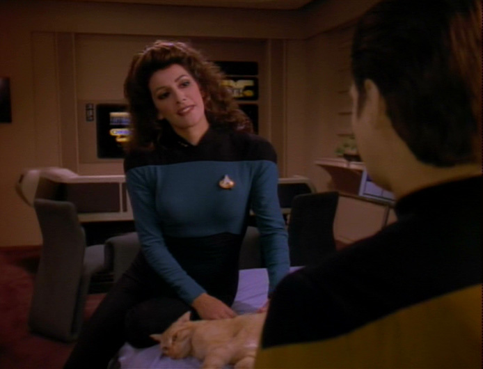 Troi perches on Data's bed next to Spot, talking to Data about dreams and Freud