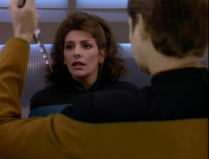 Troi looks up in fear as Data prepares to stab her in the turbolift