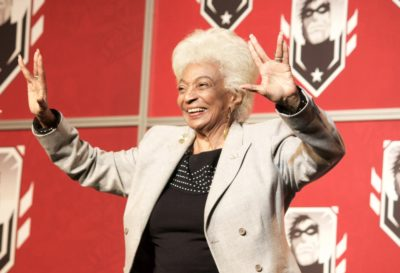 Nichelle Nichols giving the Vulcan salute with both hands on stage at a 2016 con