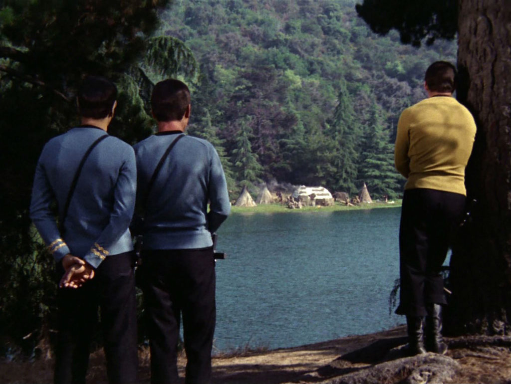 Kirk, Spock and McCoy stare across the lake at a Native American village