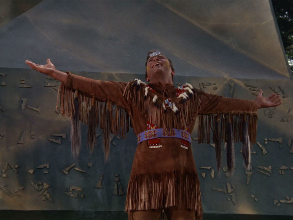 Kirk as Kirok, in buckskins and a headband spreads his arms wide