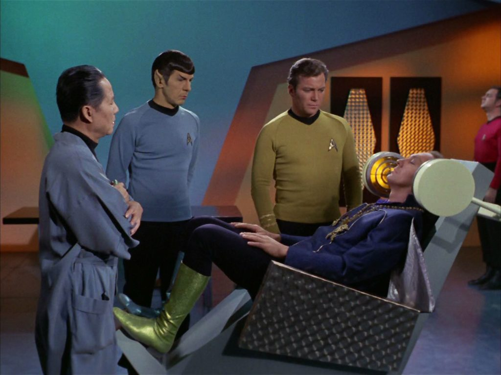 Garth in the rehabilitation chair as Cory, Spock and Kirk look on