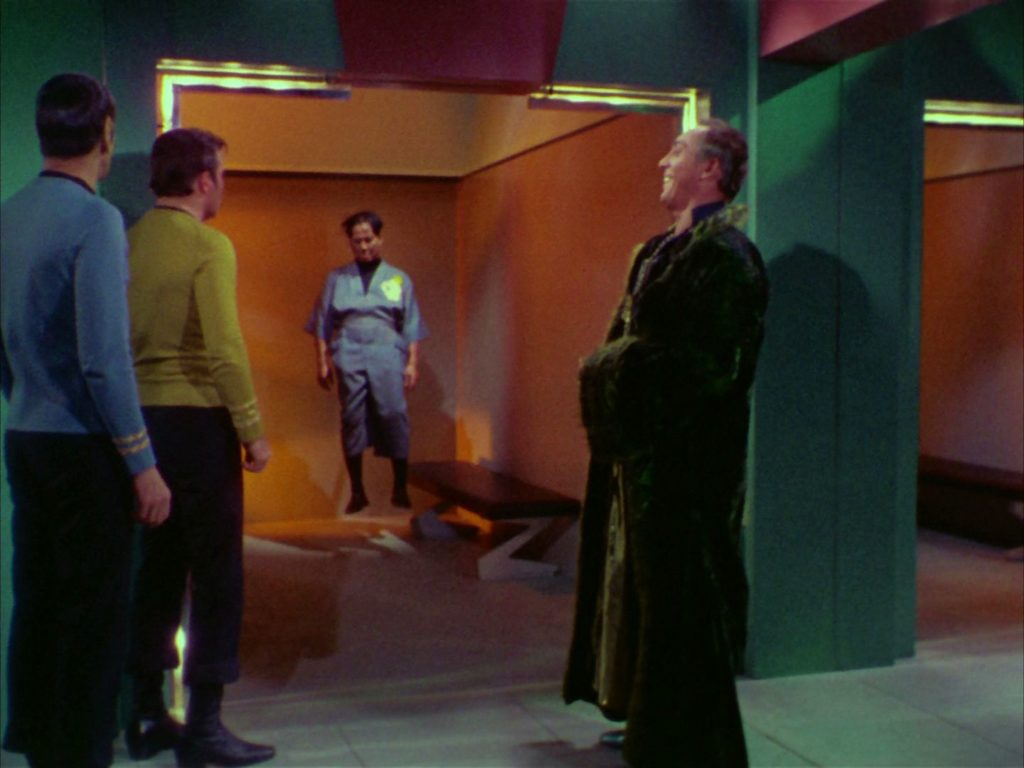 Garth, Kirk and Spock look at Governor Cory through the glass door of his holding cell