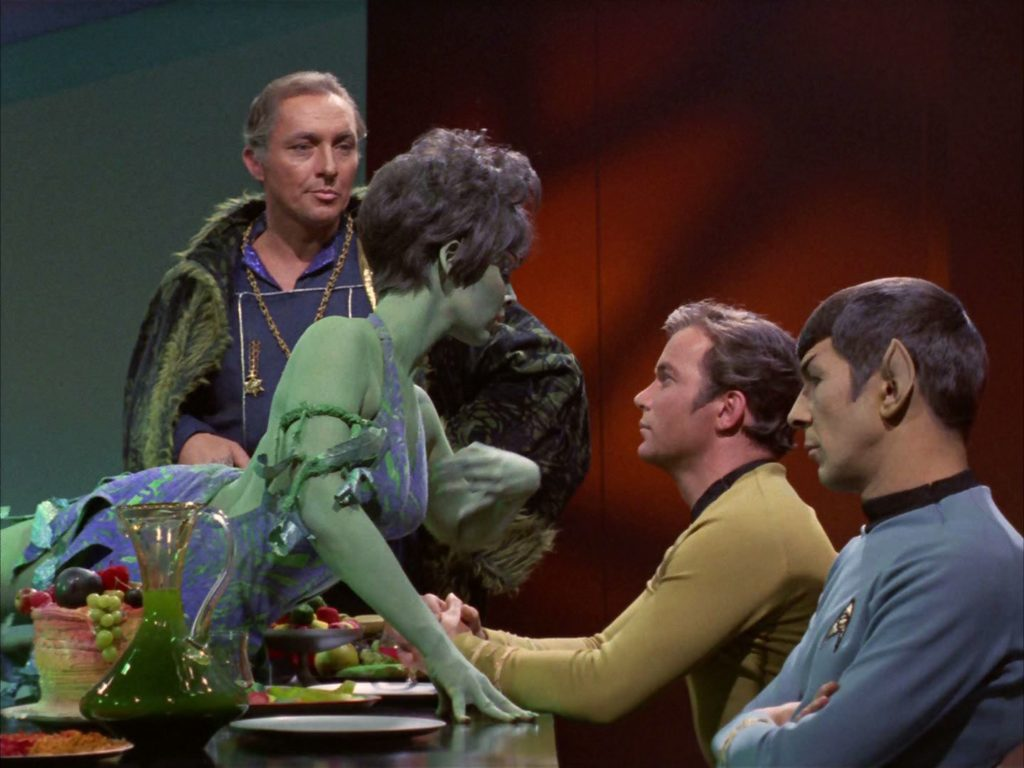 Marta dances, lying across the dinner table in front of Kirk and Spock