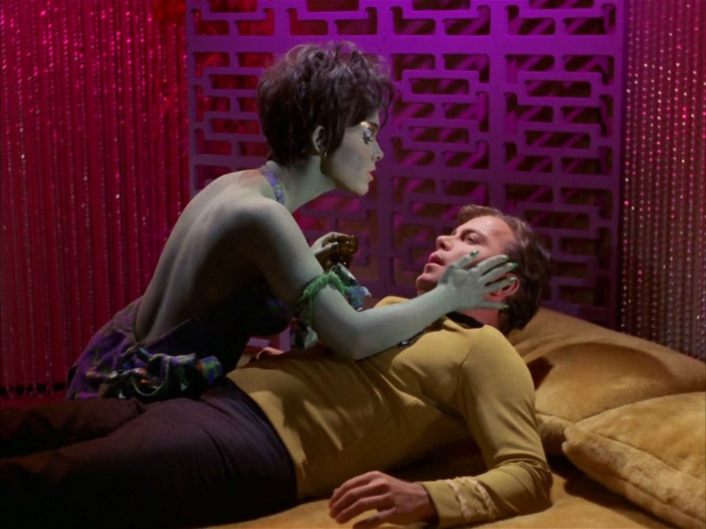 Marta touches Kirk's face as he lies on a velvet-covered bed
