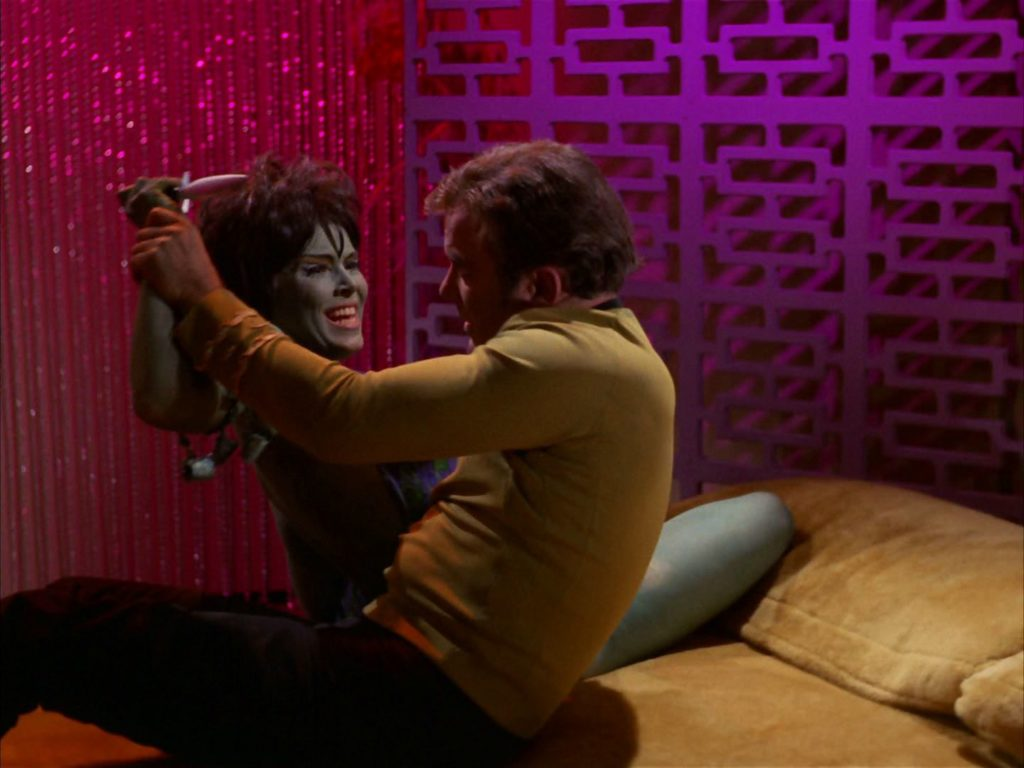 Kirk fends off Marta as she tries to stab him