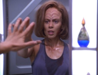 B'Elanna looks at herself in the mirror in her quarters