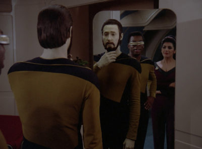 Data looking at his new beard in the mirror, while Geordi and Troi watch