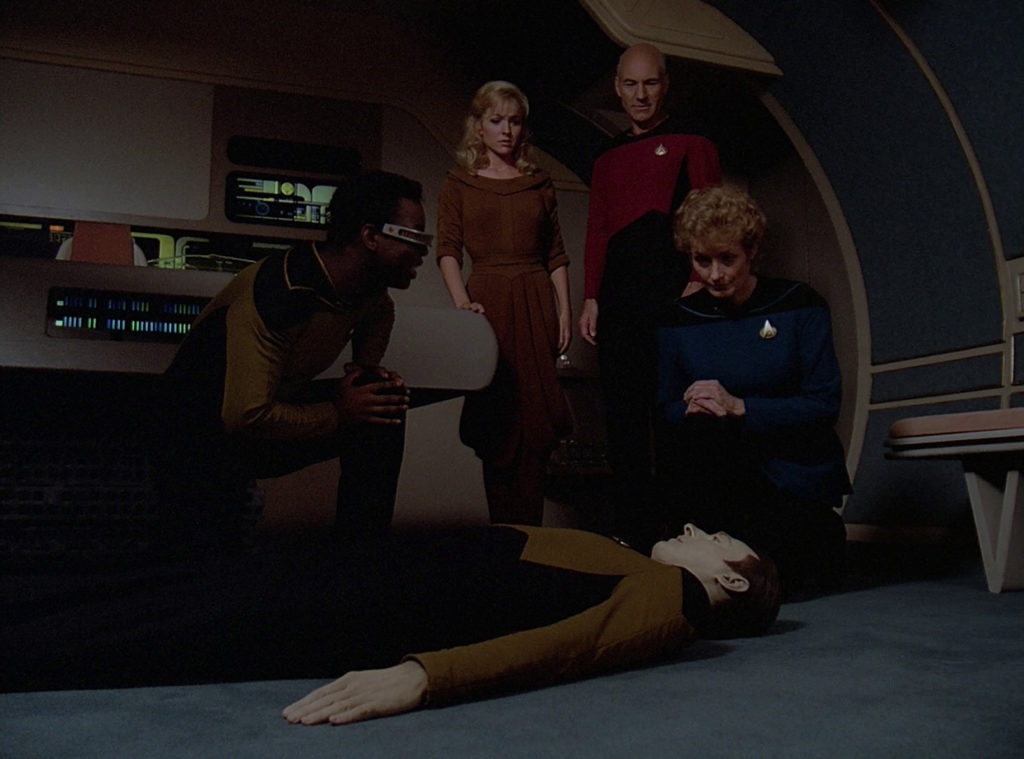 Data lying on the ground while Pulaski and La Forge kneel over him, Kareen and Picard look on